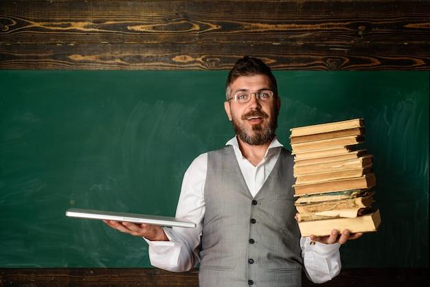 Livro de papel de e-learning de educação online contra laptop professor sorrindo segurando livros e laptop masculino