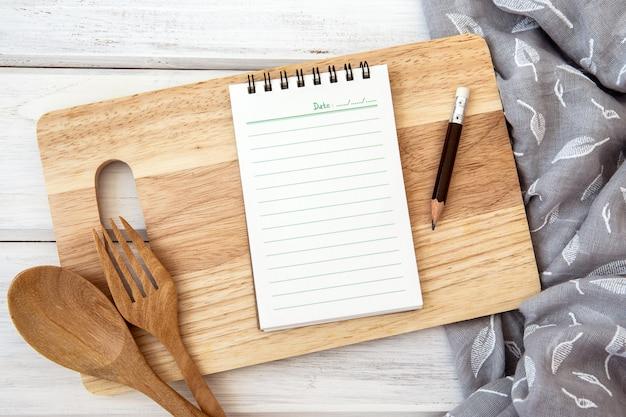 Livro de papel do bloco de notas em uma tábua de cortar e toalha de mesa na mesa branca