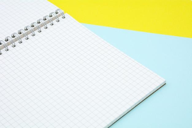 Livro de papel grade branca sobre fundo azul e amarelo