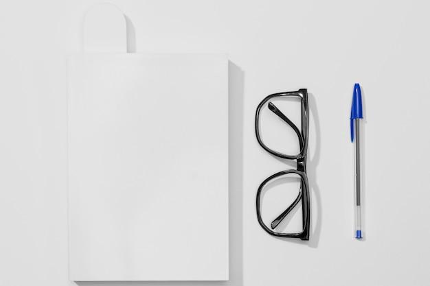 Livro de papelaria e caneta com óculos de leitura