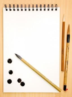 Livro de pintura com salpicos de tinta e pincéis chineses