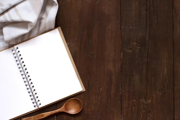 Livro de receitas culinárias em branco com colher e guardanapo em uma mesa de madeira