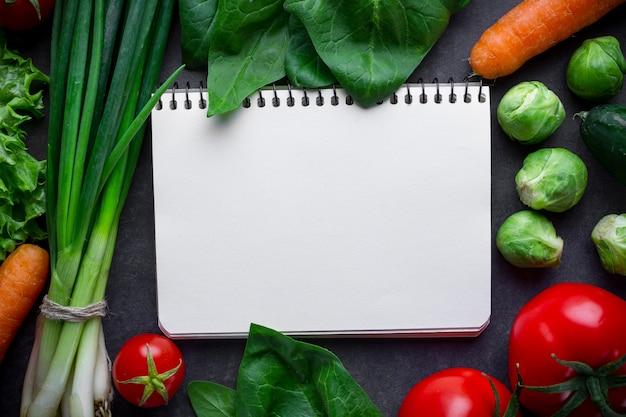Livro de receitas em branco e ingredientes para cozinhar pratos de legumes frescos e saudáveis