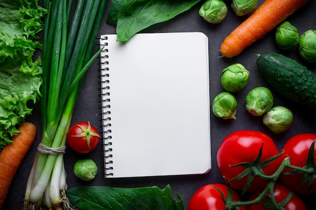 Livro de receitas em branco e vários vegetais maduros para cozinhar salada fresca e pratos saudáveis. nutrição adequada, alimentos limpos e equilibrados. plano de dieta e controle de alimentos. diário de controle