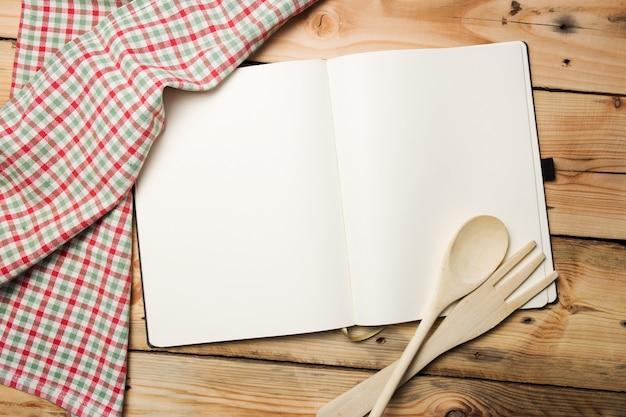 Livro de receitas em branco na mesa de madeira