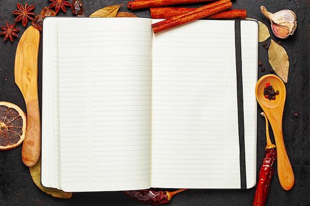 Livro de receitas, faca de madeira, colher e espécies na velha superfície rústica