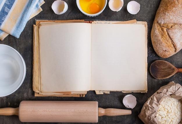 Livro de receitas vintage em branco com casca de ovo, pão, farinha, rolo de massa