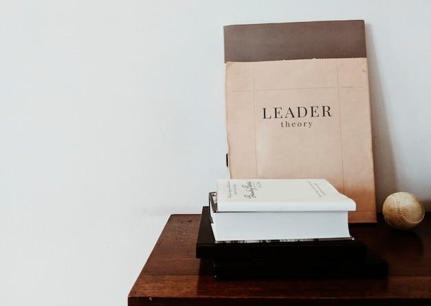 Livro de teoria de líder com uma bola de beisebol na mesa