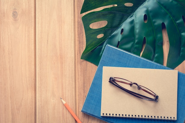 Livro de vista superior e nota de lápis na mesa de madeira