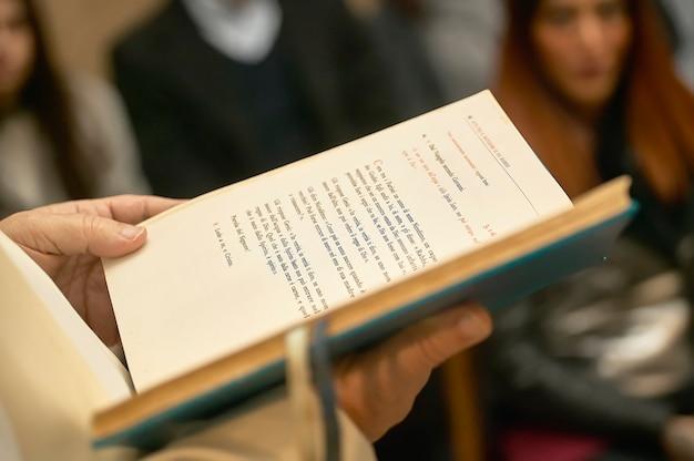 Livro do evangelho segurado pelo padre durante uma festa católica em uma igreja cheia de fiéis.