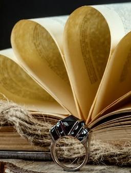 Livro e anel em cima da mesa
