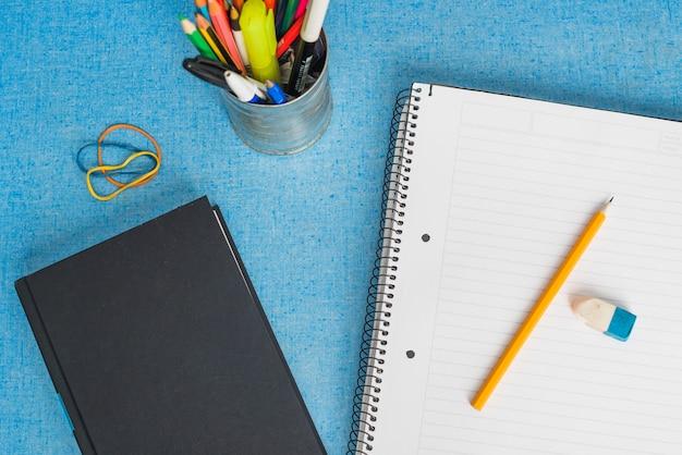 Livro e caderno perto de copo com artigos de papelaria