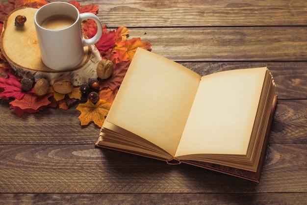 Livro e café perto de nozes e folhas