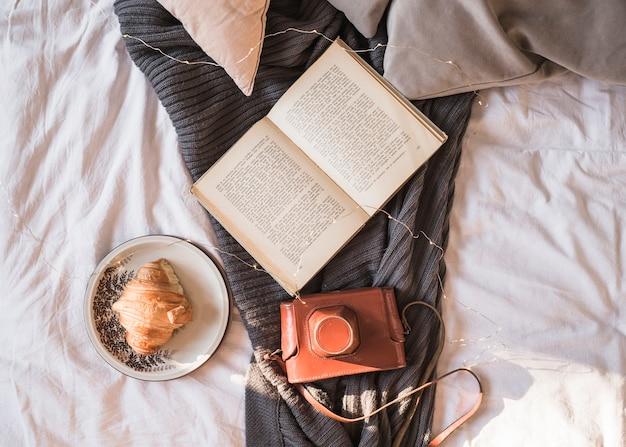 Livro e câmera fotográfica colocada no cobertor