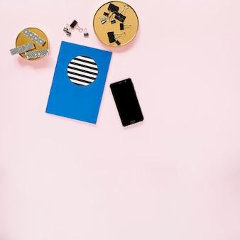Livro e celular com artigos de papelaria no fundo rosa