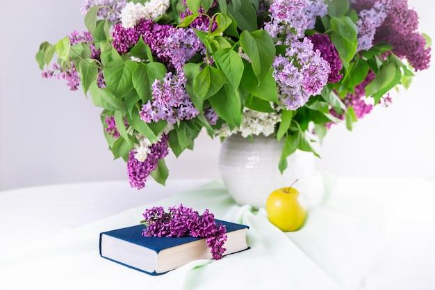 Livro e chá e um grande buquê de flores lilás