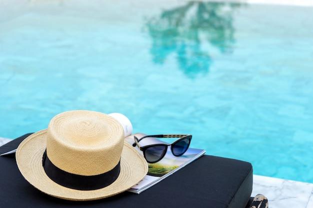 Livro e chapéu na espreguiçadeira perto da piscina,