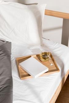Livro e copo de chá em cima da cama
