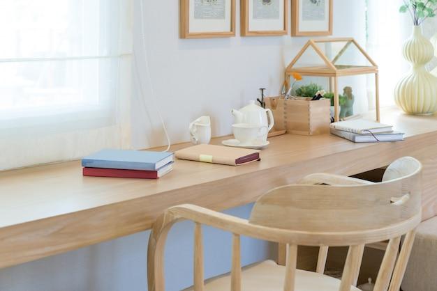 Livro e copo e frasco de café na tabela de madeira com a decoração na casa.
