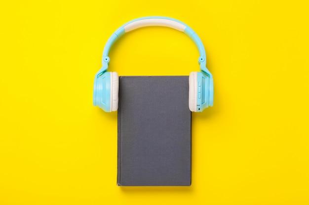 Livro e fones de ouvido em fundo amarelo.