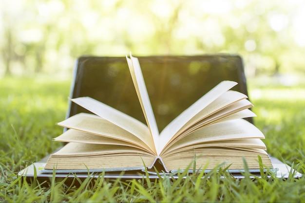 Livro e laptop no conceito de parque, conhecimento e educação