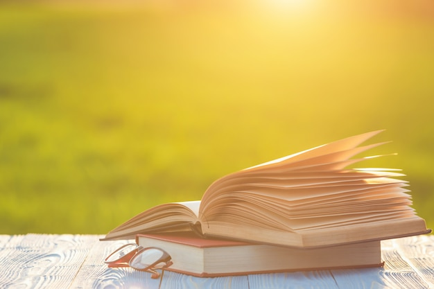 Livro e óculos na mesa de madeira com borrão abstrata e bokeh no nascer ou pôr do sol