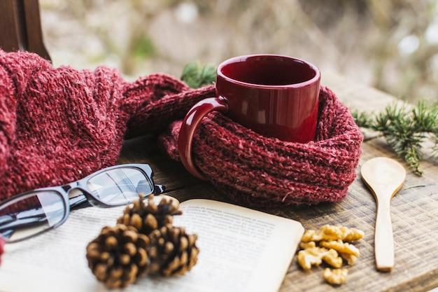 Livro e óculos perto de camisola e bebida quente