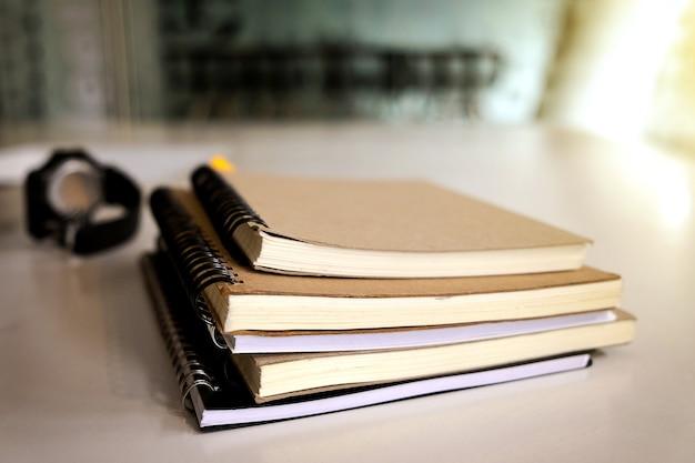 Livro e relógio de pulso na mesa de madeira com luz solar