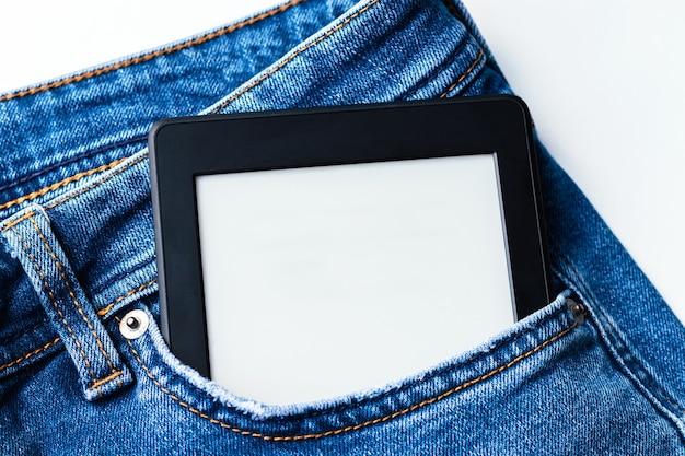 Livro eletrônico moderno com uma tela em branco no bolso da calça jeans