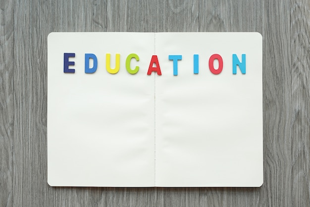 Livro em branco aberto com letras educação na tabela de madeira.