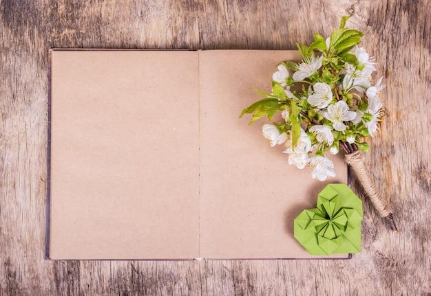 Livro em branco aberto, flores de cerejeira e coração de origami