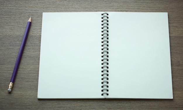 Livro espiral aberto e lápis em fundo de madeira escura