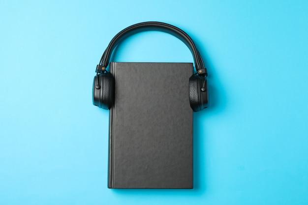 Livro fechado e fones de ouvido no espaço azul, espaço para texto