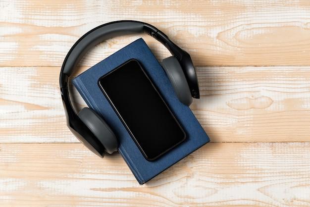 Livro, fones de ouvido e telefone em fundo de madeira. ouça o conceito de audiolivros.