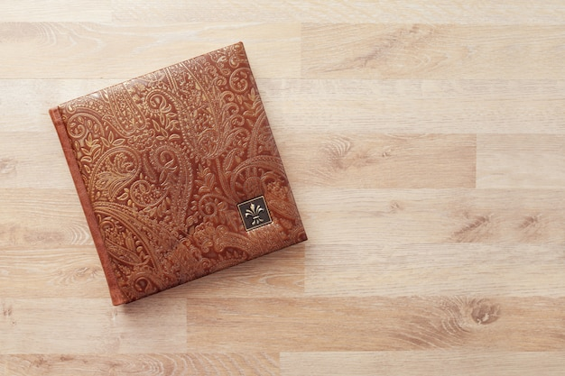 Livro fotográfico, caderno ou diário com capa de couro genuíno. cor marrom com estampagem decorativa. álbum de fotos de casamento ou família. copie o espaço.
