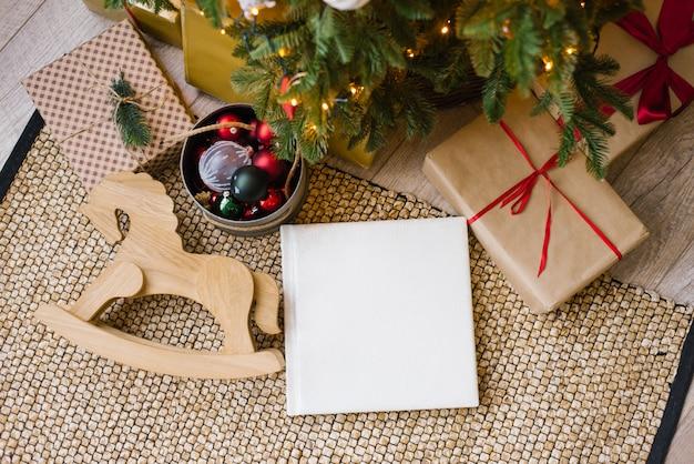 Livro fotográfico em capa de couro branco, álbum de casamento ou foto de família sob a árvore de natal, cercado por presentes de natal