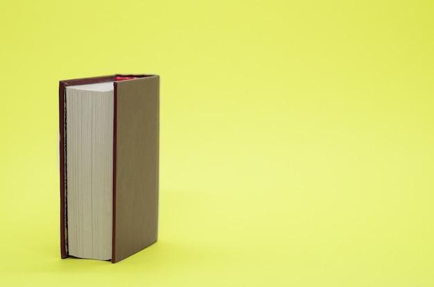 Livro grosso na parede amarela