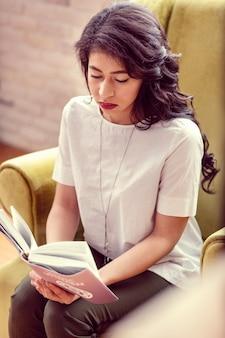 Livro interessante. vista superior de uma mulher séria e inteligente lendo um livro em casa
