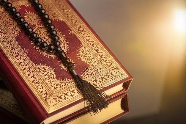 Livro islâmico do alcorão com rosário em fundo cinza