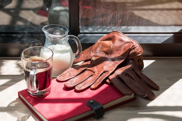 Livro, jarro de leite, luvas de couro marrom e café preto na madeira.