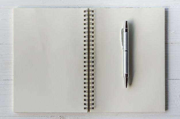 Livro marrom aberto e caneta na mesa de madeira branca
