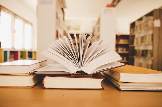 Livro na biblioteca com o velho livro aberto, pilha pilhas de arquivo de texto de literatura na mesa de leitura