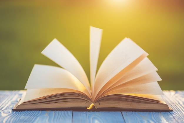 Livro na mesa de madeira com borrão abstrata e bokeh no nascer ou pôr do sol