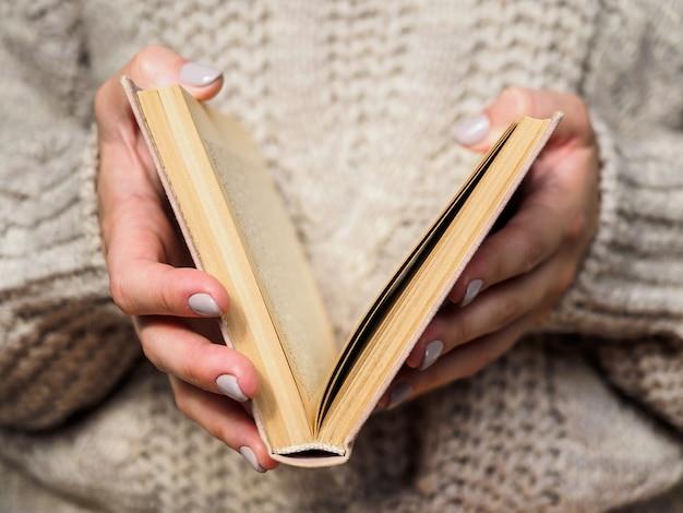 Livro nas mãos das mulheres. uma garota com um suéter de lã está segurando um livro. atmosfera acolhedora.