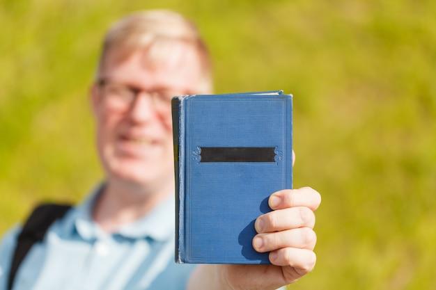 Livro nas mãos do homem, num gesto de doação