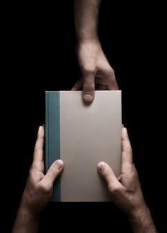 Livro nas mãos masculinas em um preto