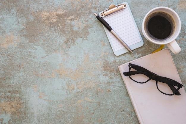 Livro; óculos; prancheta; caneta e xícara de café sobre fundo rústico