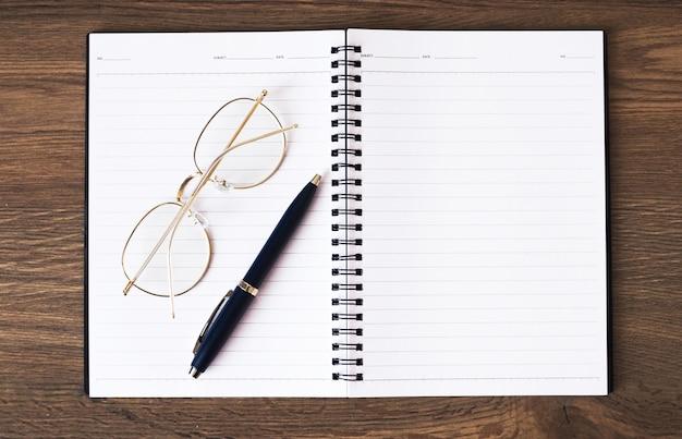 Livro para nota, óculos e caneta colocada sobre uma mesa de madeira