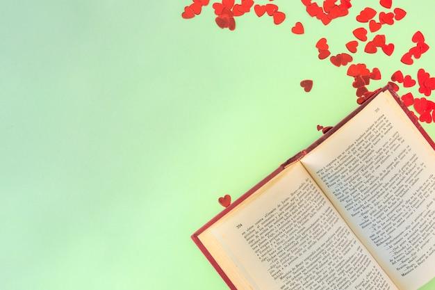 Livro perto de conjunto de corações de papel de ornamento