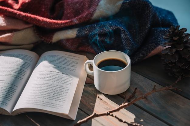 Livro perto de xícara e manta de lã na mesa